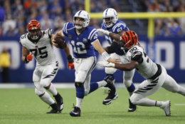 Indianapolis Colts quarterback Andrew Luck (12) is chased by Cincinnati Bengals defensive end Jordan Willis (75) and defensive end Michael Johnson (90) during the second half of an NFL football game in Indianapolis, Sunday, Sept. 9, 2018. The Bengals defeated the Colts 34-23. (AP Photo/Jeff Roberson)