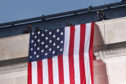 A U.S. flag is unfurled at sunrise Tuesday, Sept. 11, 2018, at the Pentagon on the 17th anniversary of the Sept. 11, 2001, terrorist attacks. (AP Photo/Pablo Martinez Monsivais)