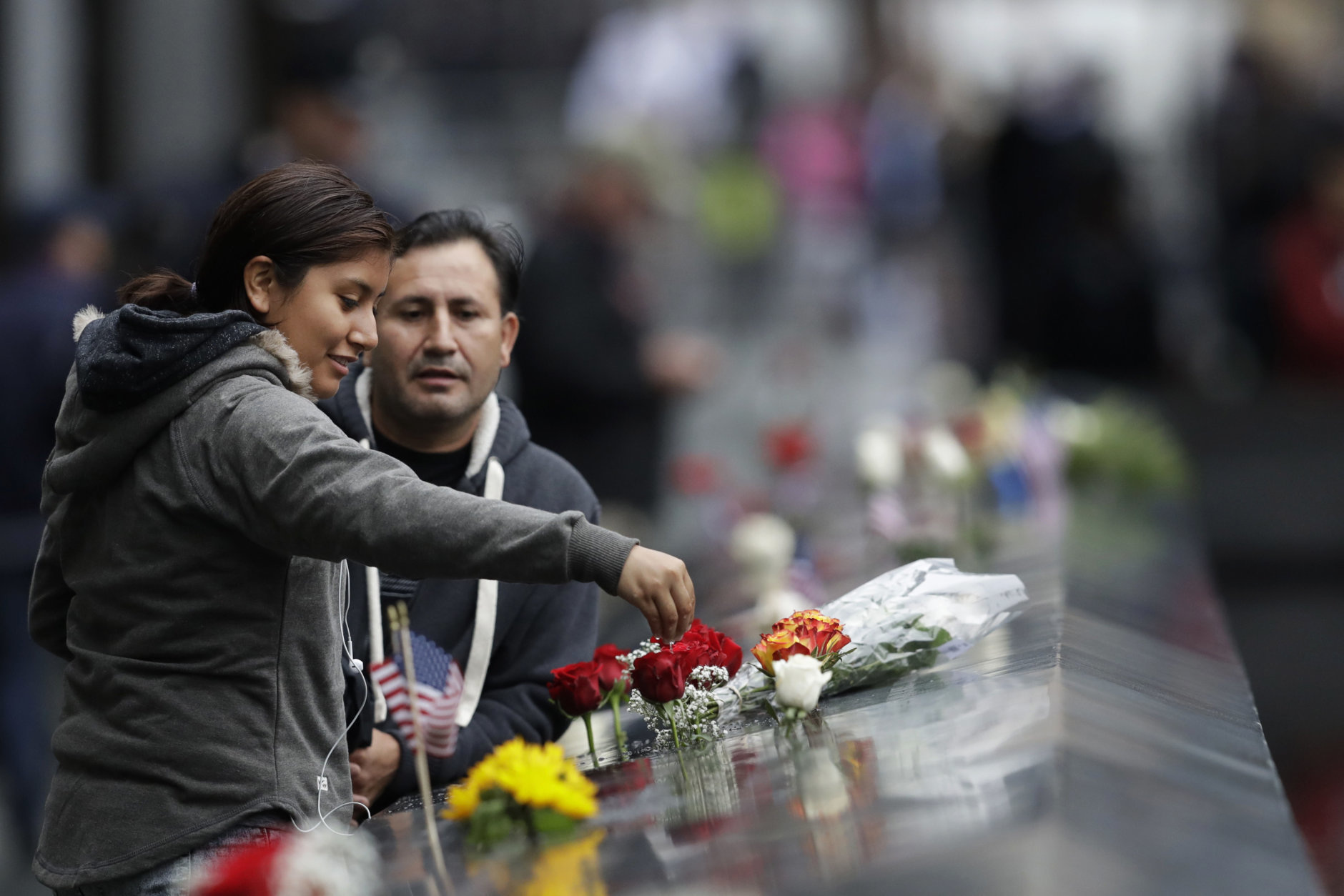 A woman drips water on a bouquet of flowers at the North Pool during a ceremony marking the 17th anniversary of the terrorist attacks on the United States on Tuesday, Sept. 11, 2018, in New York. (AP Photo/Mark Lennihan)