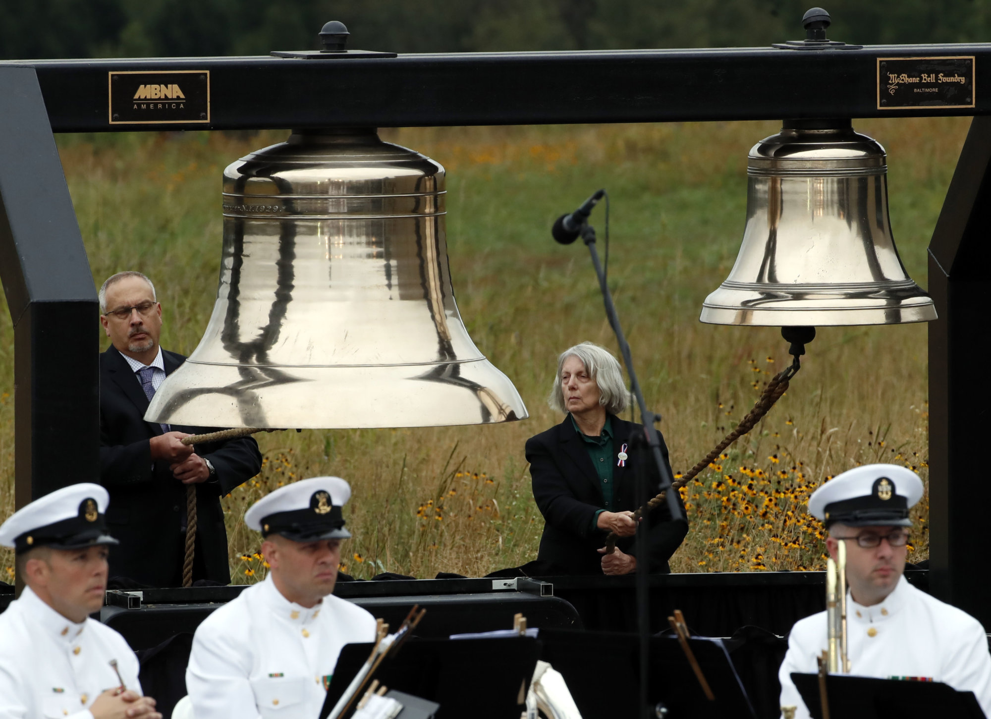 Bill Anders, left, and Sharon Custer ring bells as part of the Name Presentation and Ringing of Bells Remembrance during the September 11th Flight 93 Memorial Service in Shanksville, Pa., attended by President Donald Trump and first lady Melania Trump, Tuesday, Sept. 11, 2018. (AP Photo/Gene J. Puskar)