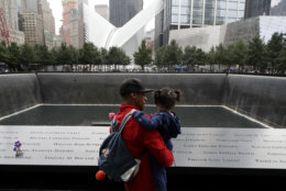 A man talks with a girl as they look at the North Pool at the World Trade Center during a ceremony marking the 17th anniversary of the terrorist attacks on the United States, Tuesday, Sept. 11, 2018, in New York. (AP Photo/Mark Lennihan)