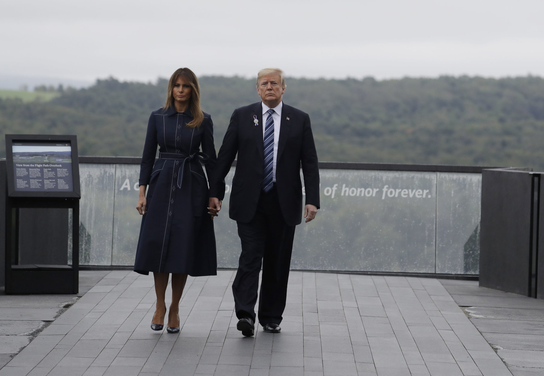 President Donald Trump and first lady Melania Trump, walk along the September 11th Flight 93 memorial, Tuesday, Sept. 11, 2018, in Shanksville, Pa., escorted by  (AP Photo/Evan Vucci)