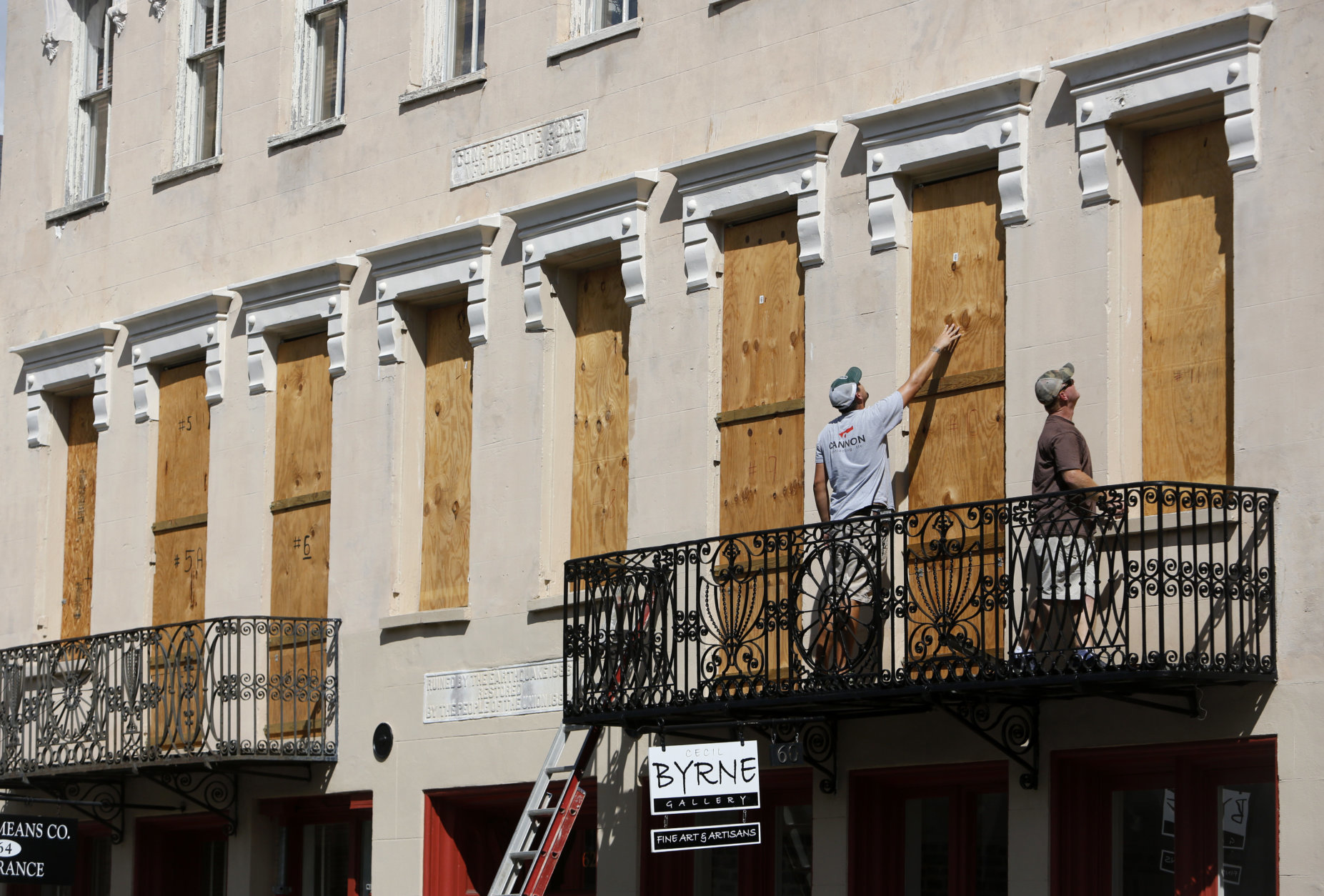 Derek Mundy, left, and Kris Crouse boards up the Confederate House in preparation for Hurricane Florence in downtown Charleston, S.C., Tuesday, Sept. 11, 2018. (AP Photo/Mic Smith)