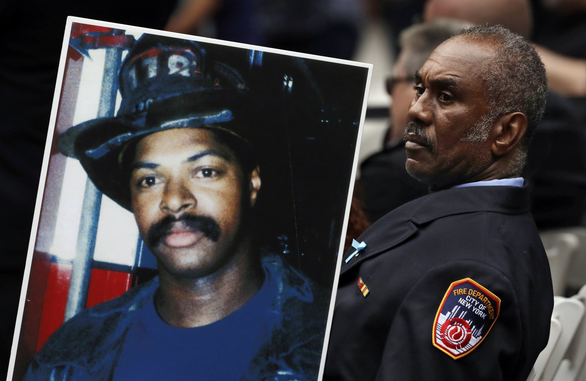 Retired New York firefighter Bruce Stanley carries a photograph of fellow firefighter Liam Smith Jr. during a ceremony, Tuesday, Sept. 11, 2018, in New York, at the World Trade Center, marking the 17th anniversary of the terrorist attacks on the United States. Smith was one of 343 members of the fire department who were killed on Sept. 11, 2001. (AP Photo/Mark Lennihan)