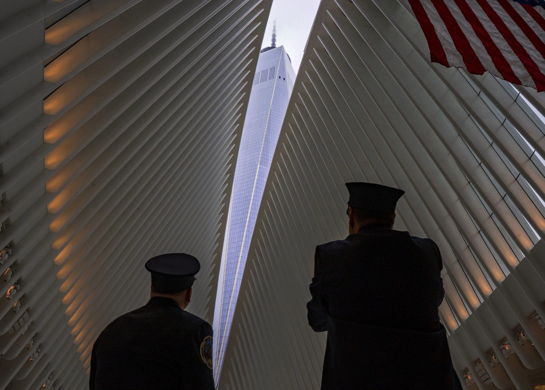 Two members of the New York City fire department look towards One World Trade Center through the open ceiling of the Oculus, part of the World Trade Center transportation hub in New York, Tuesday, Sept. 11, 2018, the anniversary of 9/11 terrorist attacks. The transit hall ceiling window was opened just before 10:28 a.m., marking the moment that the North Tower of the World Trade Center collapsed on September 11, 2001. (AP Photo/Craig Ruttle)
