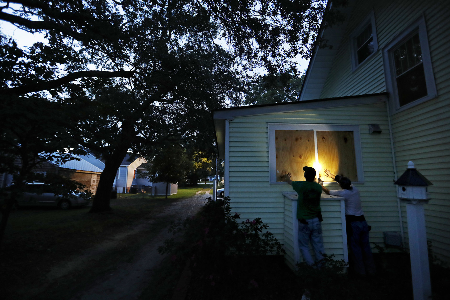 Russell Meadows, left, helps neighbor Rob Muller board up his home ahead of Hurricane Florence in Morehead City, N.C., Tuesday, Sept. 11, 2018. Florence exploded into a potentially catastrophic hurricane Monday as it closed in on North and South Carolina, carrying winds up to 140 mph (220 kph) and water that could wreak havoc over a wide stretch of the eastern United States later this week. (AP Photo/David Goldman)
