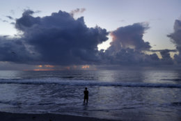 A woman stands in the surf and looks at the clouds at sunrise as Hurricane Florence approaches in Wrightsville Beach, N.C., Wednesday, Sept. 12, 2018. (AP Photo/Chuck Burton)
