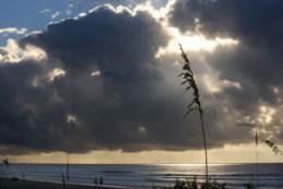 "People walk the beach as the early morning sun streaks through clouds on the beach at the Isle of Palms, S.C., as Hurricane Florence spins out in the Atlantic ocean Wednesday, Sept. 12, 2018.  The National Weather Service says Hurricane Florence ""will likely be the storm of a lifetime for portions of the Carolina coast."" (AP Photo/Mic Smith)"