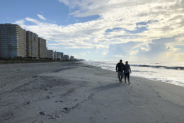 Chris and Nicole Roland walk down a beach in North Myrtle Beach, S.C. on Wednesday, Sept. 12, 2018. The couple boarded up their uncle's condominium and are leaving soon as Hurricane Florence approaches. (AP Photo/Jeffery Collins)