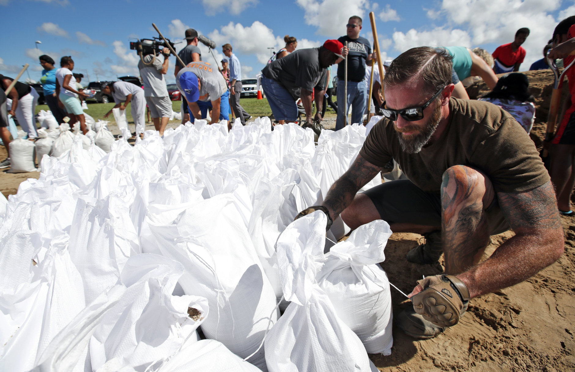 Brady Osborne ties freshly filled sandbags, Wednesday, Sept. 12, 2018, in Virginia Beach, Va., as Hurricane Florence moves towards the eastern shore. (AP Photo/Alex Brandon)