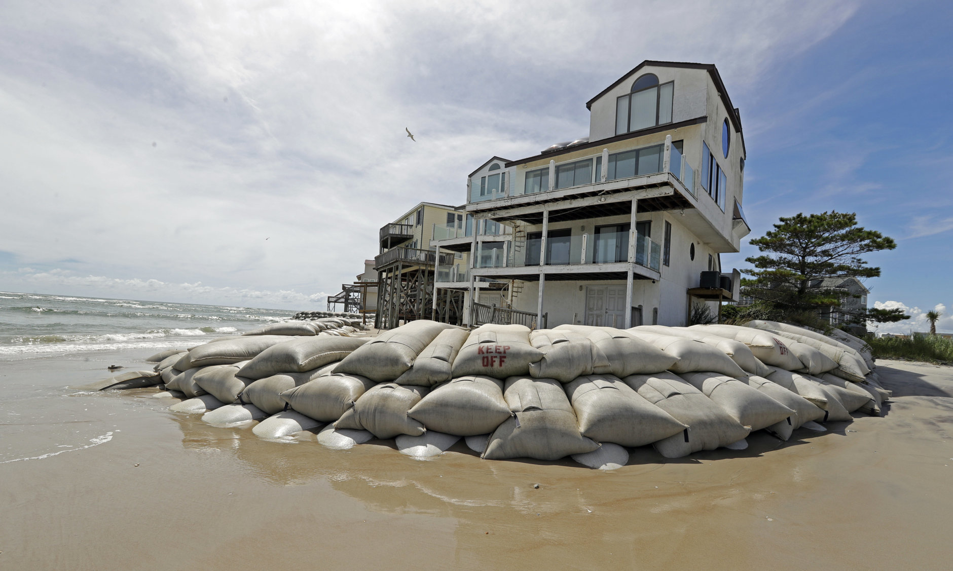 Sand bags surround homes on North Topsail Beach, N.C., Wednesday, Sept. 12, 2018, as Hurricane Florence threatens the coast. (AP Photo/Chuck Burton)