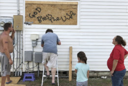 In this Wednesday, Sept. 12, 2018, photo Mercedes O'Neill, right, her 6-year-old daughter Sophie, her boyfriend Kelly Johnson, left and neighbor Shawn Dalton on ladder put plywood on the window of their home in North Myrtle Beach, S.C. O'Neill thought a long time about evacuating from Hurricane Florence but decided they couldn't afford it. (AP Photo/Jeffrey Collins)