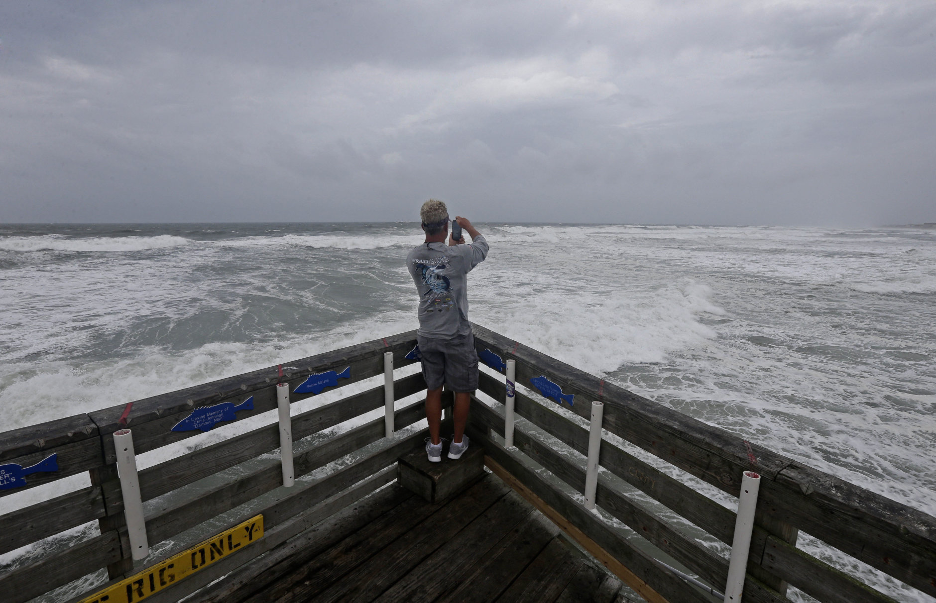 Patrick Wells looks out over the Atlantic ocean at the Avalon Fishing Pier in Kill Devil Hills, N.C., Thursday, Sept. 13, 2018 as Hurricane Florence approaches the east coast. (AP Photo/Gerry Broome)