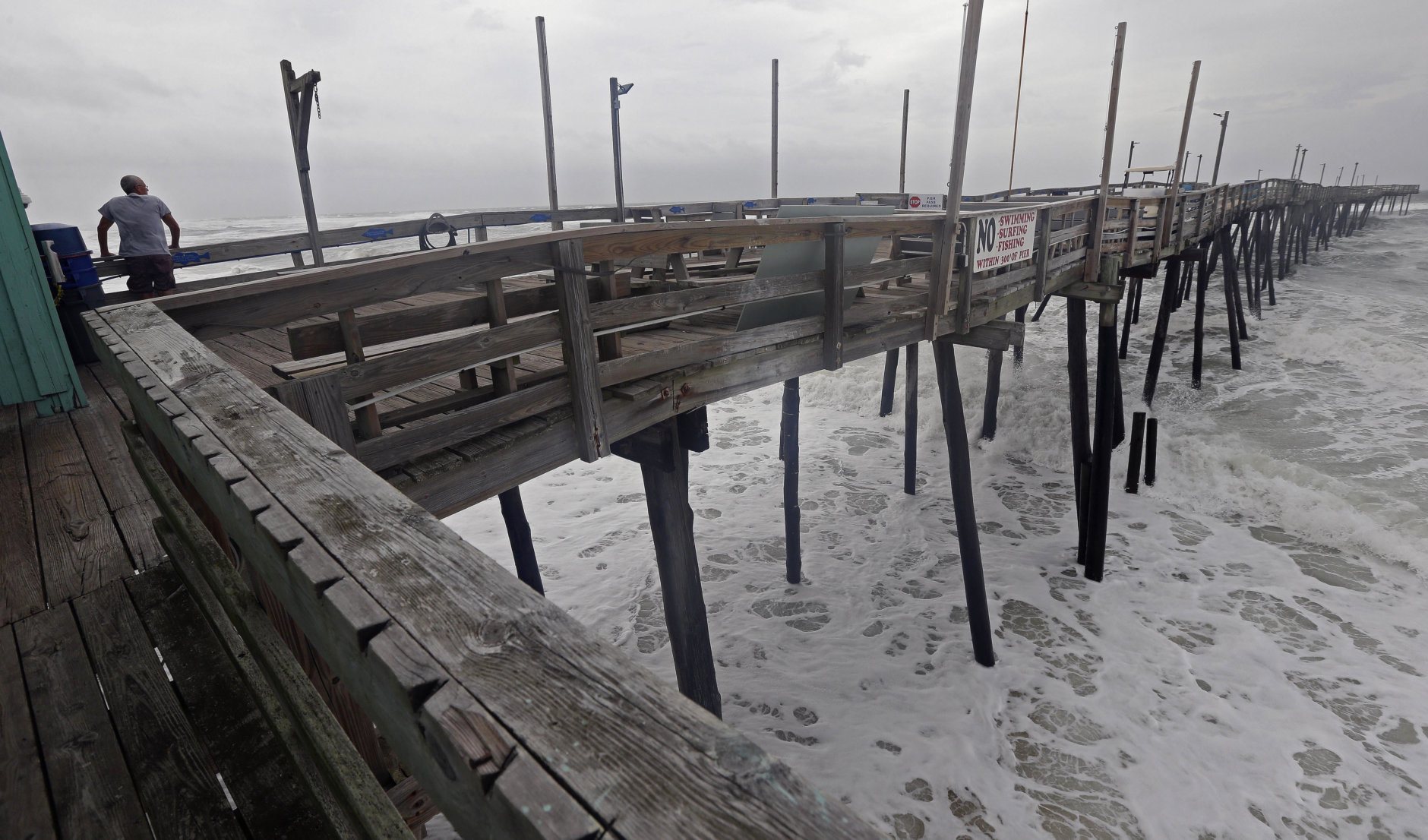 Waves crash under the Avalon Fishing Pier in Kill Devil Hills, N.C., Thursday, Sept. 13, 2018 as Hurricane Florence approaches the east coast. (AP Photo/Gerry Broome)
