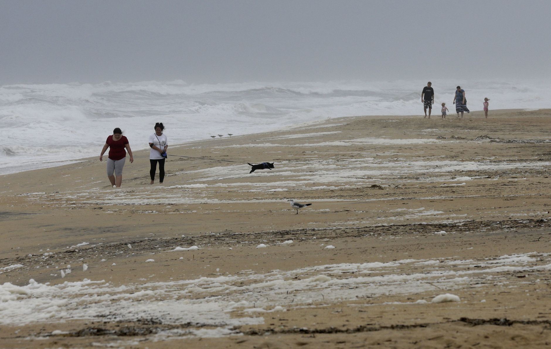 People walk the beach in Kill Devil Hills, N.C., Thursday, Sept. 13, 2018 as Hurricane Florence approaches the east coast. (AP Photo/Gerry Broome)