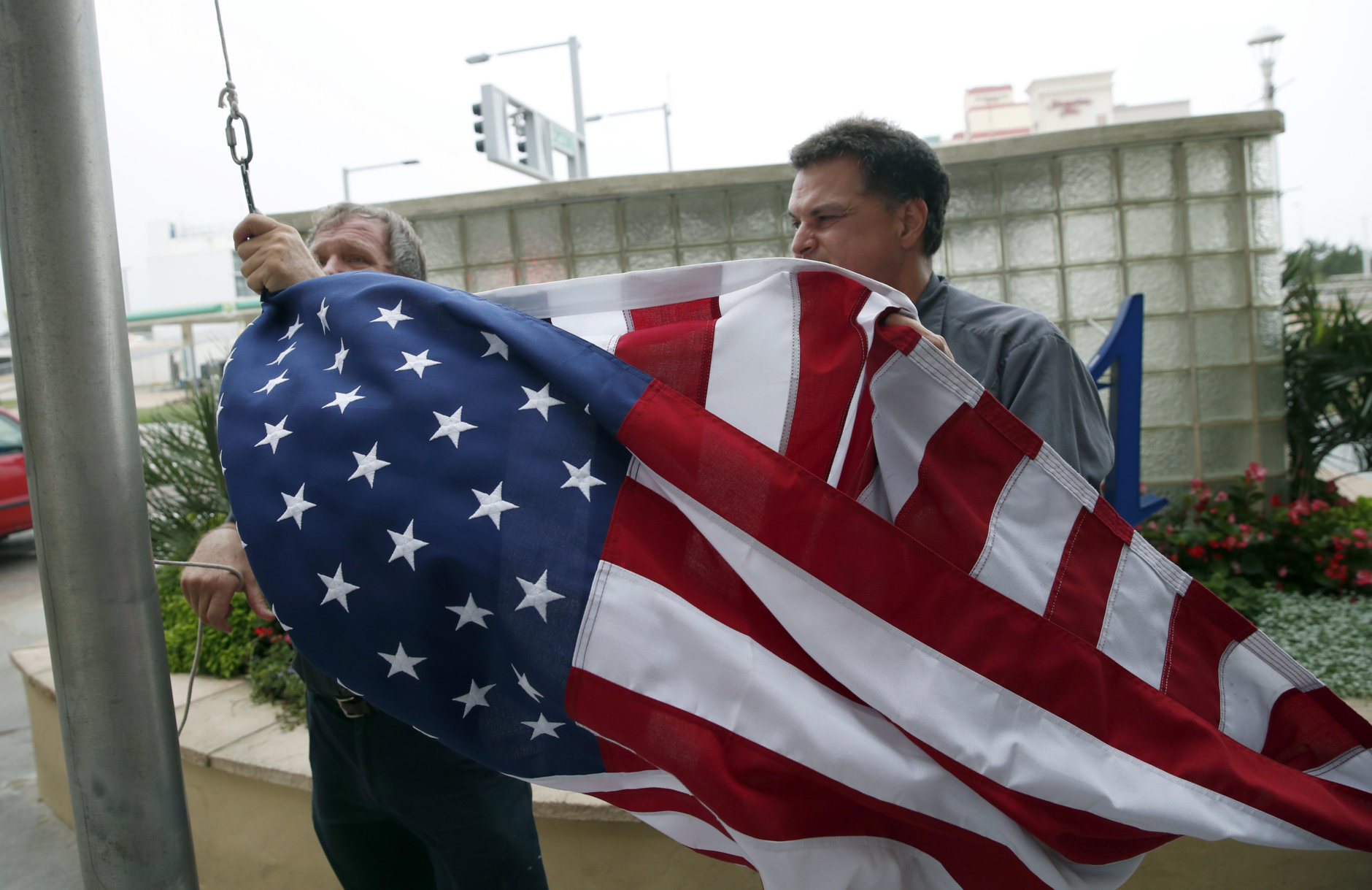 Jim Mehlich, left, and Hans Seda, both with the Hilton Hotel, work to pull down an American flag in windy conditions, Thursday, Sept. 13, 2018, in Virginia Beach, Va., as Hurricane Florence moves towards the eastern shore. (AP Photo/Alex Brandon)
