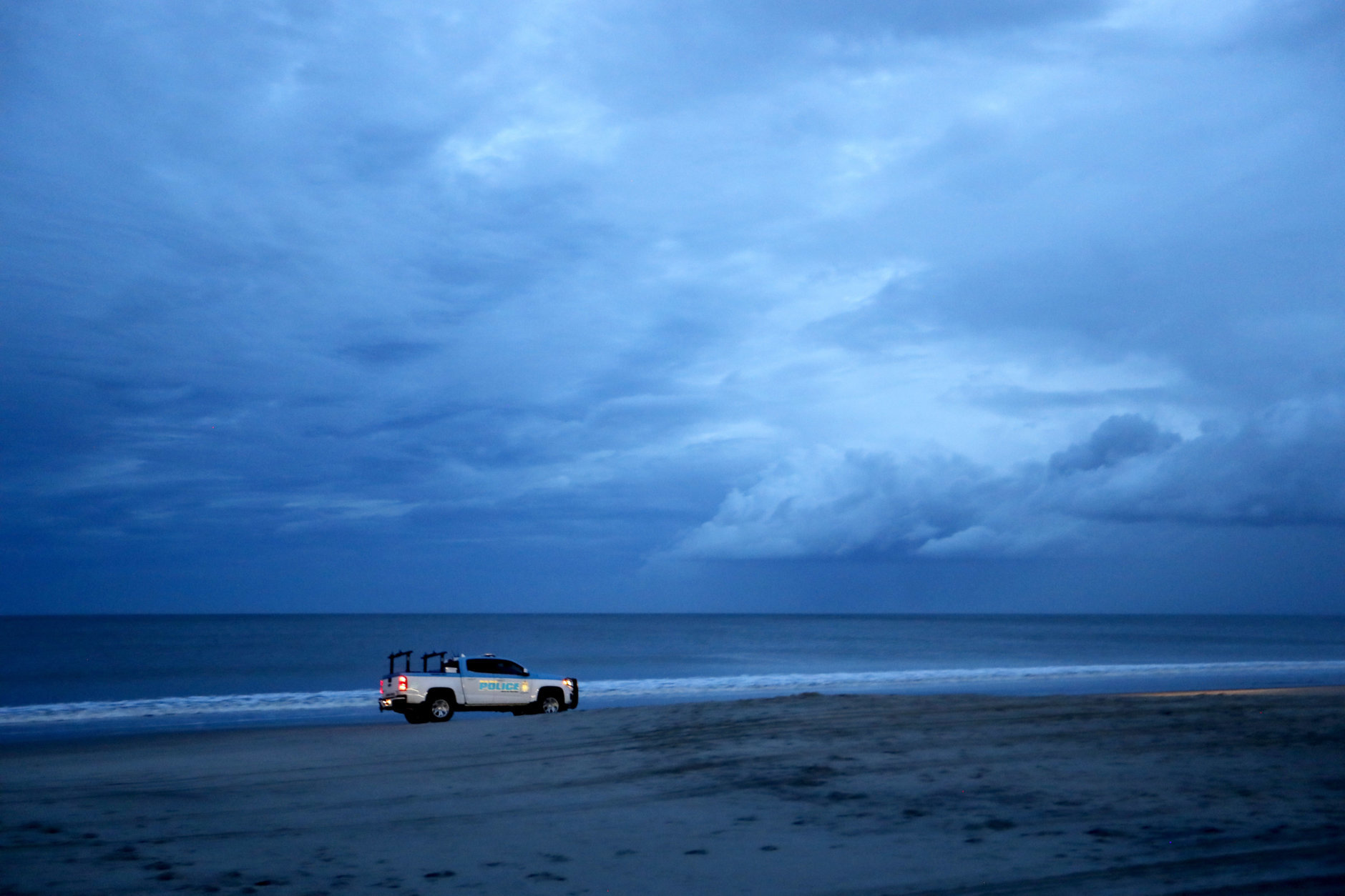 A police vehicle patrols the beach after an evening curfew went into effect as Hurricane Florence approaches Myrtle Beach, S.C., Thursday, Sept. 13, 2018. (AP Photo/David Goldman)