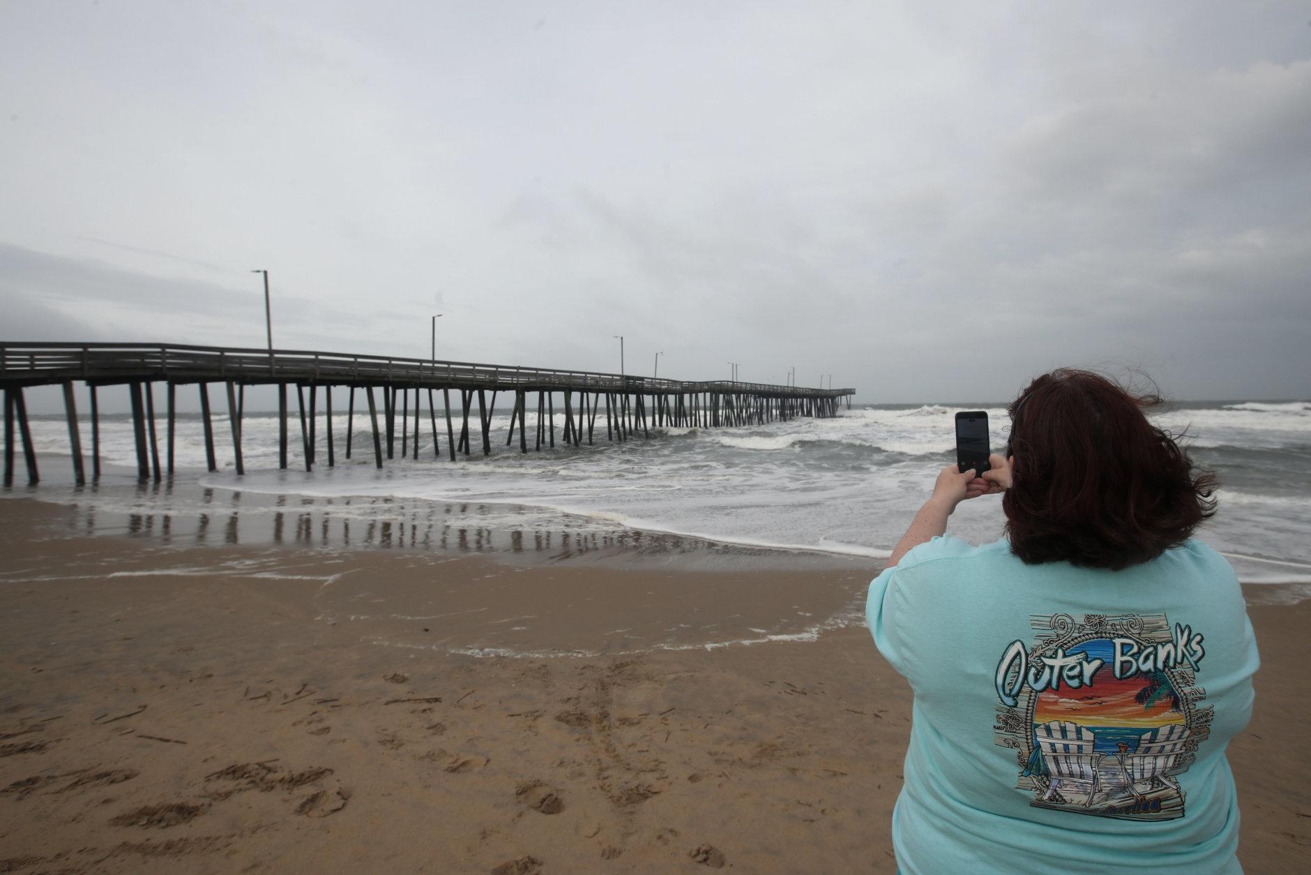 Lisa Postlewait, from Virginia Beach, Va., takes a picture near the Virginia Beach Fishing Pier , Thursday, Sept. 13, 2018, in Virginia Beach, Va., as Hurricane Florence moves towards the eastern shore. (AP Photo/Alex Brandon)