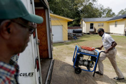 Stoney Williamson, right, unloads a generator for his brother-in-law, rear, whose home flooded two years ago from Hurricane Matthew, as Harry Campbell, left, looks on in Nichols, S.C., Thursday, Sept. 13, 2018, as Hurricane Florence approaches the east coast. (AP Photo/David Goldman)