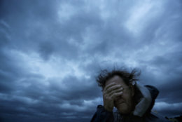 Russ Lewis covers his eyes from a gust of wind and a blast of sand as Hurricane Florence approaches Myrtle Beach, S.C., Friday, Sept. 14, 2018. (AP Photo/David Goldman)