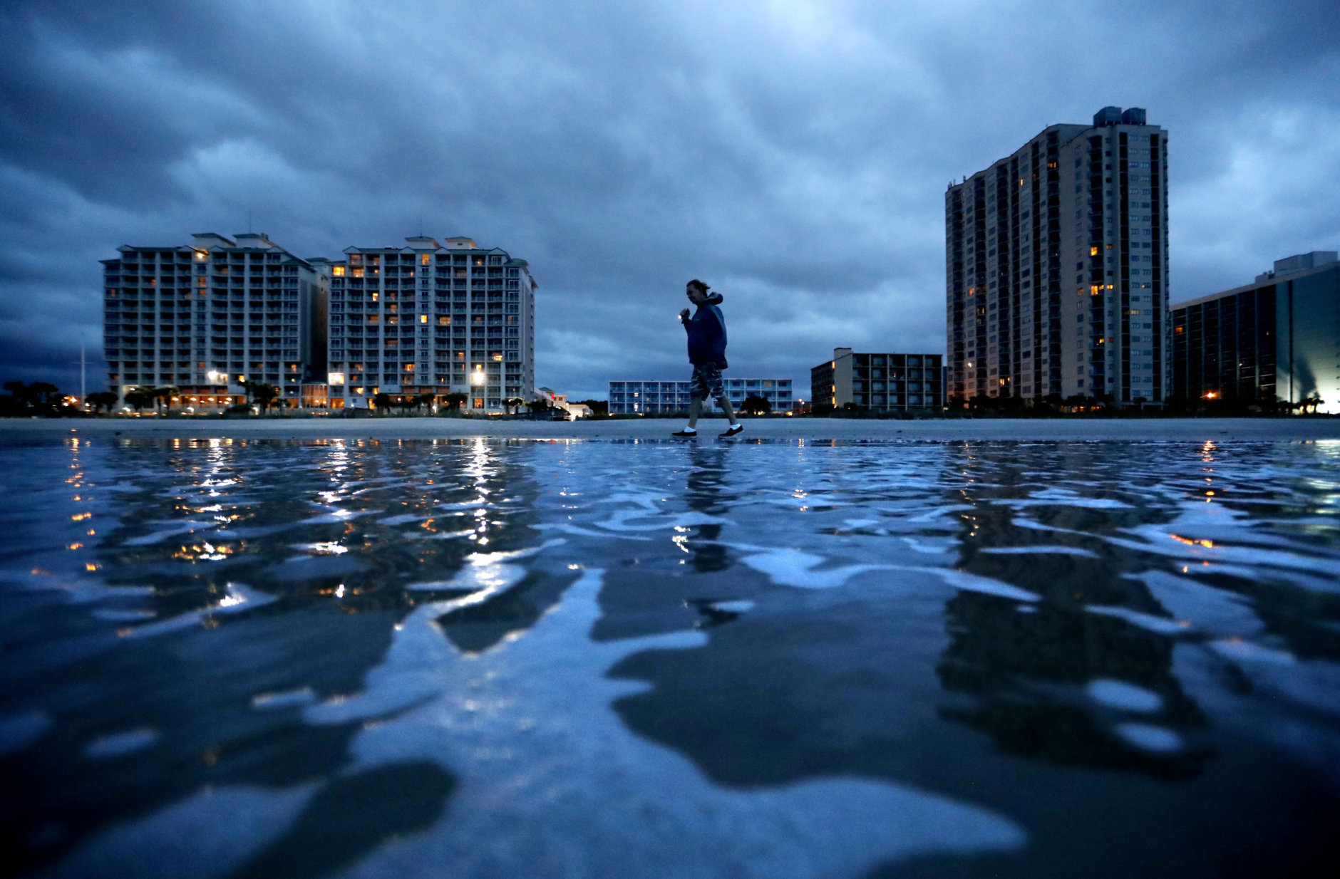 """Russ Lewis looks for shells along the beach as Hurricane Florence approaches Myrtle Beach, S.C., Friday, Sept. 14, 2018. """"We might get lucky we might not we'll find out,"""" said Lewis of the storm. (AP Photo/David Goldman)"""