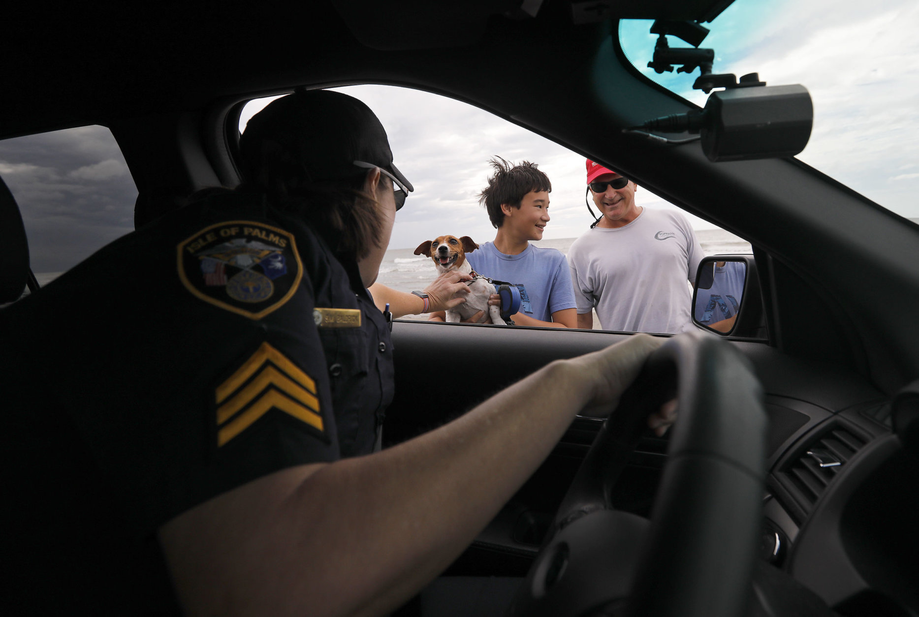 Isle of Palms police officer Detective Sergeant Sharon Baldrick speaks with Isle of Palms residents James Sireci, at right, and his son Aaron as she pets their family dog, Allie, on the Isle of Palms, S.C., as Hurricane Florence moves ashore near Wilmington, N.C., Friday, Sept. 14, 2018. (AP Photo/Mic Smith)