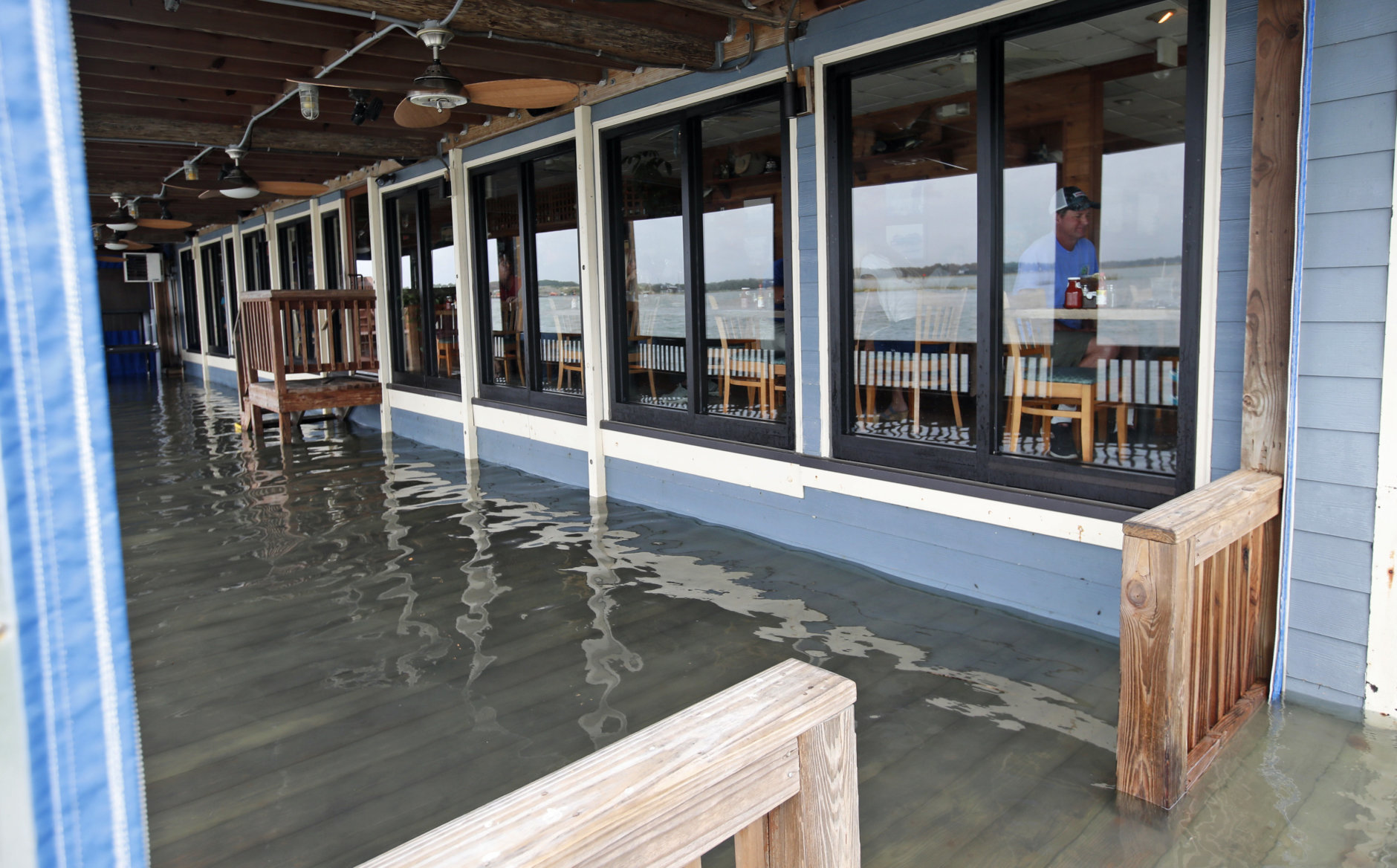 Sean Hayes, right, from Manteo, N.C., eats at Bubba's Seafood Restaurant with his family as the deck is covered with a few inches of water from effects of Hurricane Florence Friday, Sept. 14, 2018, in Virginia Beach, Va.  (AP Photo/Alex Brandon)