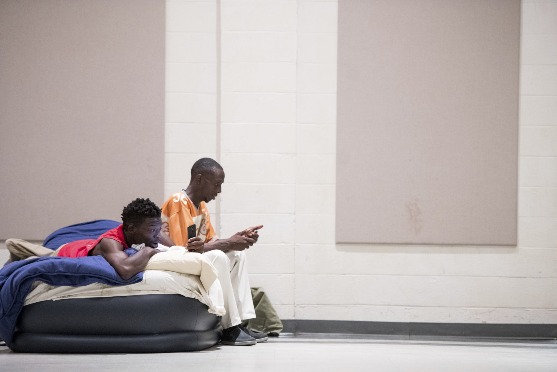 Eric Edwards Jr., left, and Elliott Farmer Jr. look at their phones from a blow up mattress at a storm shelter at Washington Street United Methodist Church as Florence slowly moves across the East Coast Friday, Sept. 14, 2018, in Columbia, S.C. Florence already has proven deadly with its nearly nonstop rain, surging seawater and howling winds, and the threat is days from ending as remnants of the hurricane slowly creep inland across the Carolinas. (AP Photo/Sean Rayford)