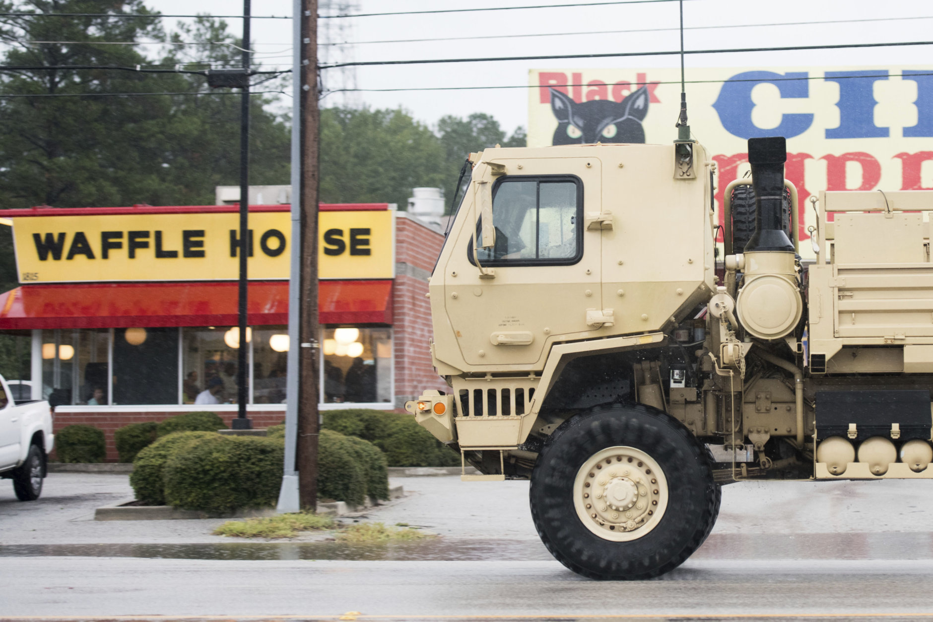 A National Guard vehicle drives past a Waffle House as Hurricane Florence slowly moves across the East Coast Friday, Sept. 14, 2018, in Florence, S.C. (AP Photo/Sean Rayford)