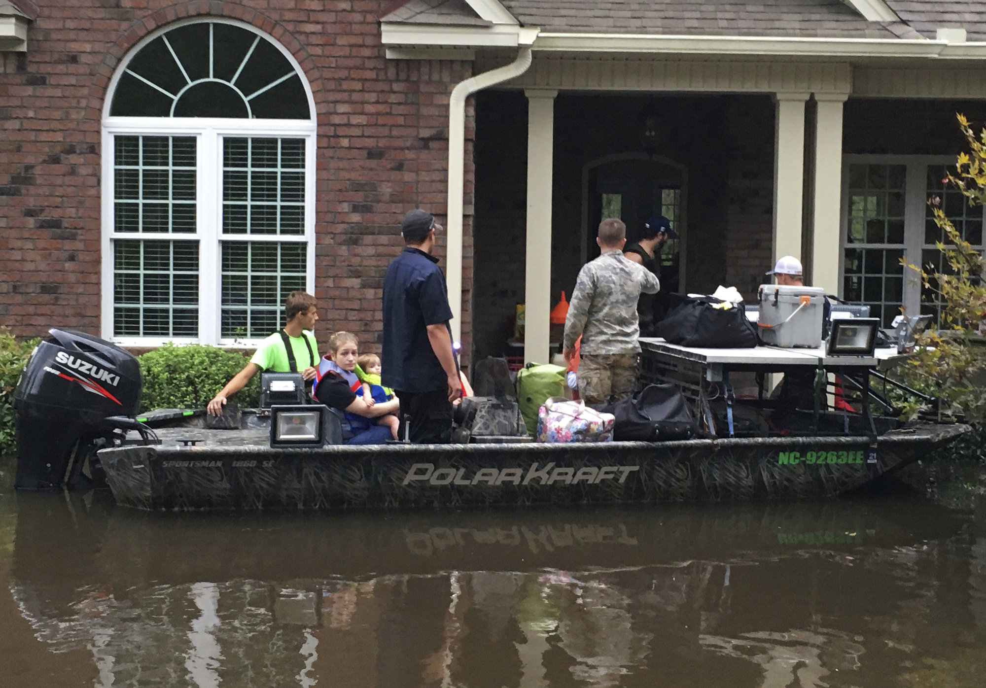 Authorities evacuate a family from rising waters caused by Florence, now a tropical storm, on Saturday, Sept. 15, 2018 in New Bern, N.C.  (AP Photo/Allen G. Breed)