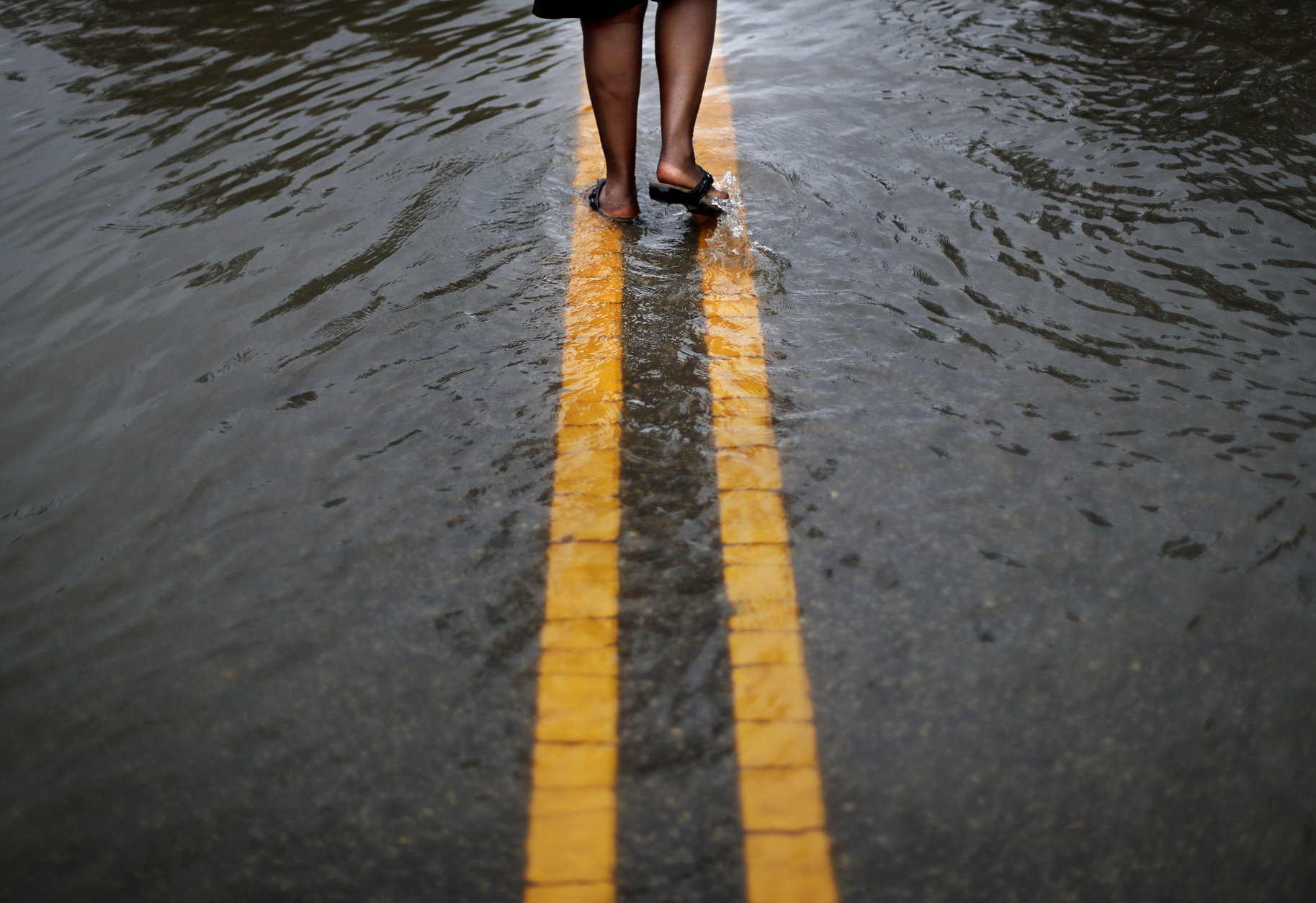 "Helen McKoy walks down a flooded street in her neighborhood as Florence continues to dump heavy rain in Fayetteville, N.C., Sunday, Sept. 16, 2018. ""I've never seen it like this before,"" said McCoy of the rising water down the street from her home. ""Whatever God got for me he's going to give it to me. He said he's going to take care of us and that's what I'm going to have to live on."" (AP Photo/David Goldman)"
