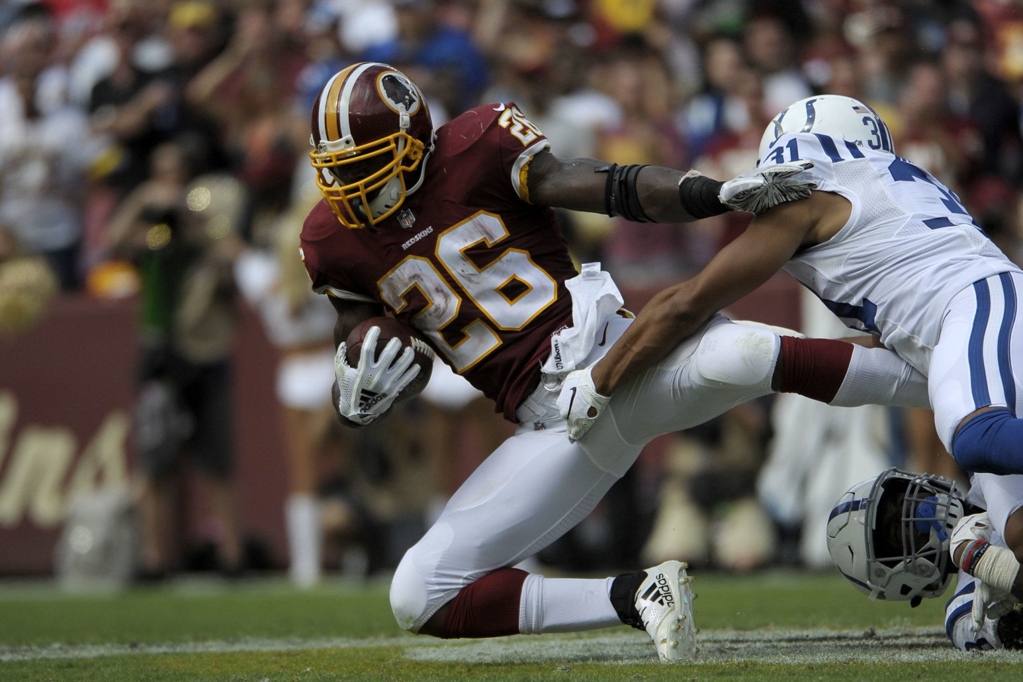 Washington Redskins running back Adrian Peterson (left) is tackled by Indianapolis Colts cornerback Quincy Wilson (right) during an NFL football game between the Indianapolis Colts and Washington Redskins, Sunday, Sept. 16, 2018, in Landover, Md. (AP Photo/Mark Tenally)