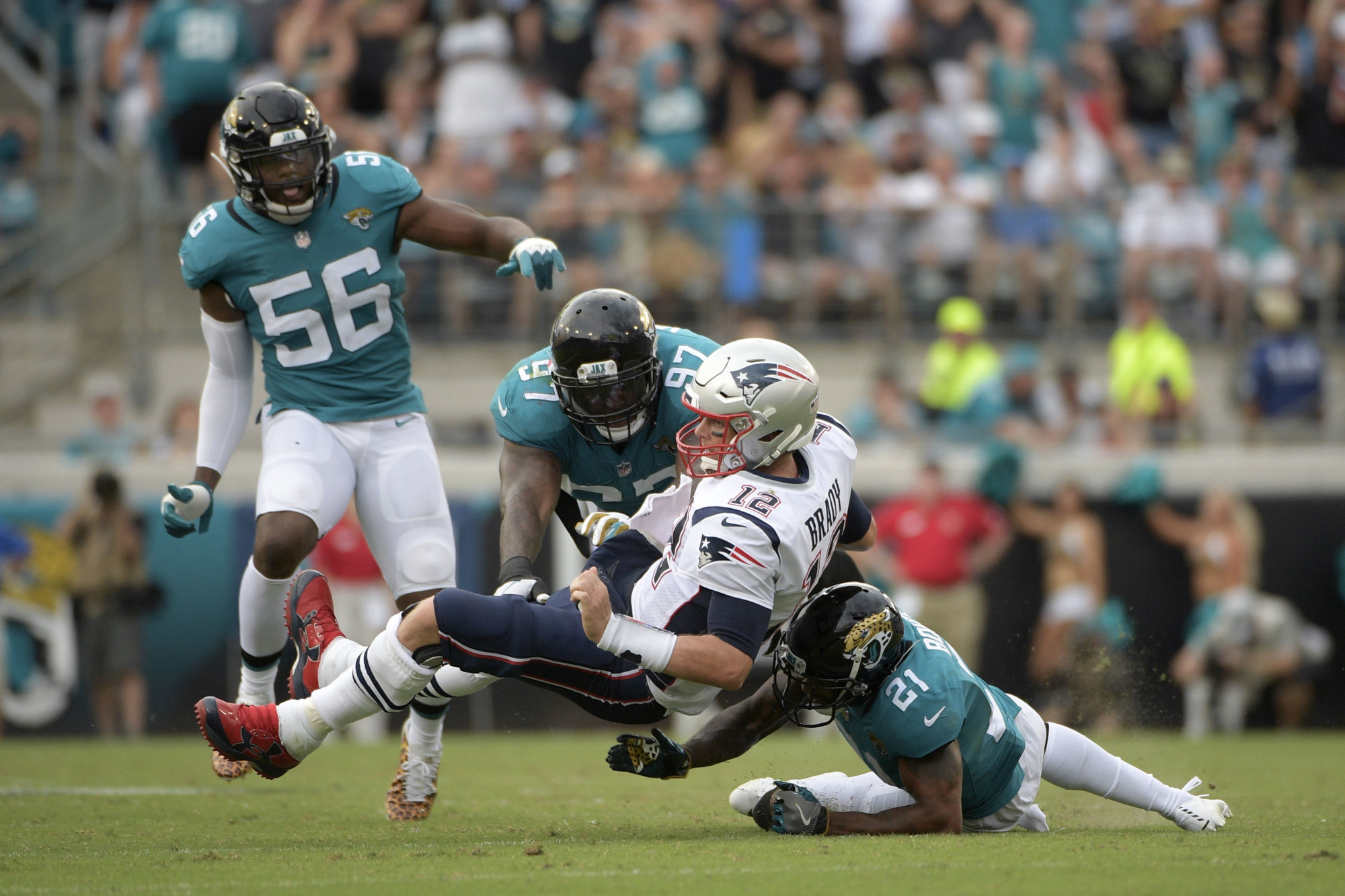 New England Patriots quarterback Tom Brady (12) is tackled after scrambling for yardage by Jacksonville Jaguars defensive tackle Malik Jackson (97) and defensive back A.J. Bouye (21), as defensive end Dante Fowler (56) trails the play, during the second half of an NFL football game Sunday, Sept. 16, 2018, in Jacksonville, Fla. The Jaguars won 31-20. (AP Photo/Phelan M. Ebenhack)