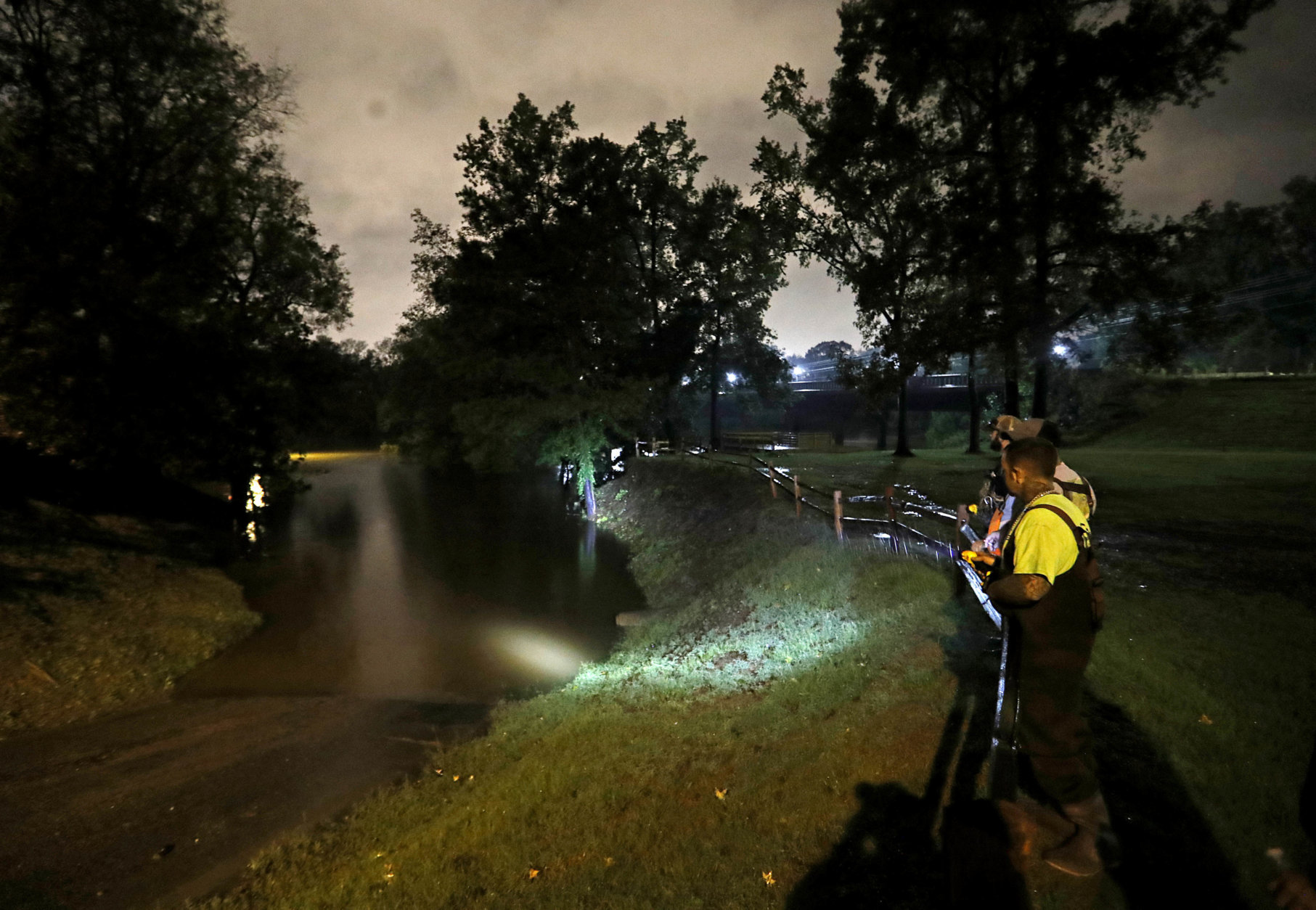 A group of local fishermen keep an eye on the Cape Fear River as they stage for potential water rescues while additional flooding remains a threat from Florence, in Fayetteville, N.C., Sunday, Sept. 16, 2018. (AP Photo/David Goldman)
