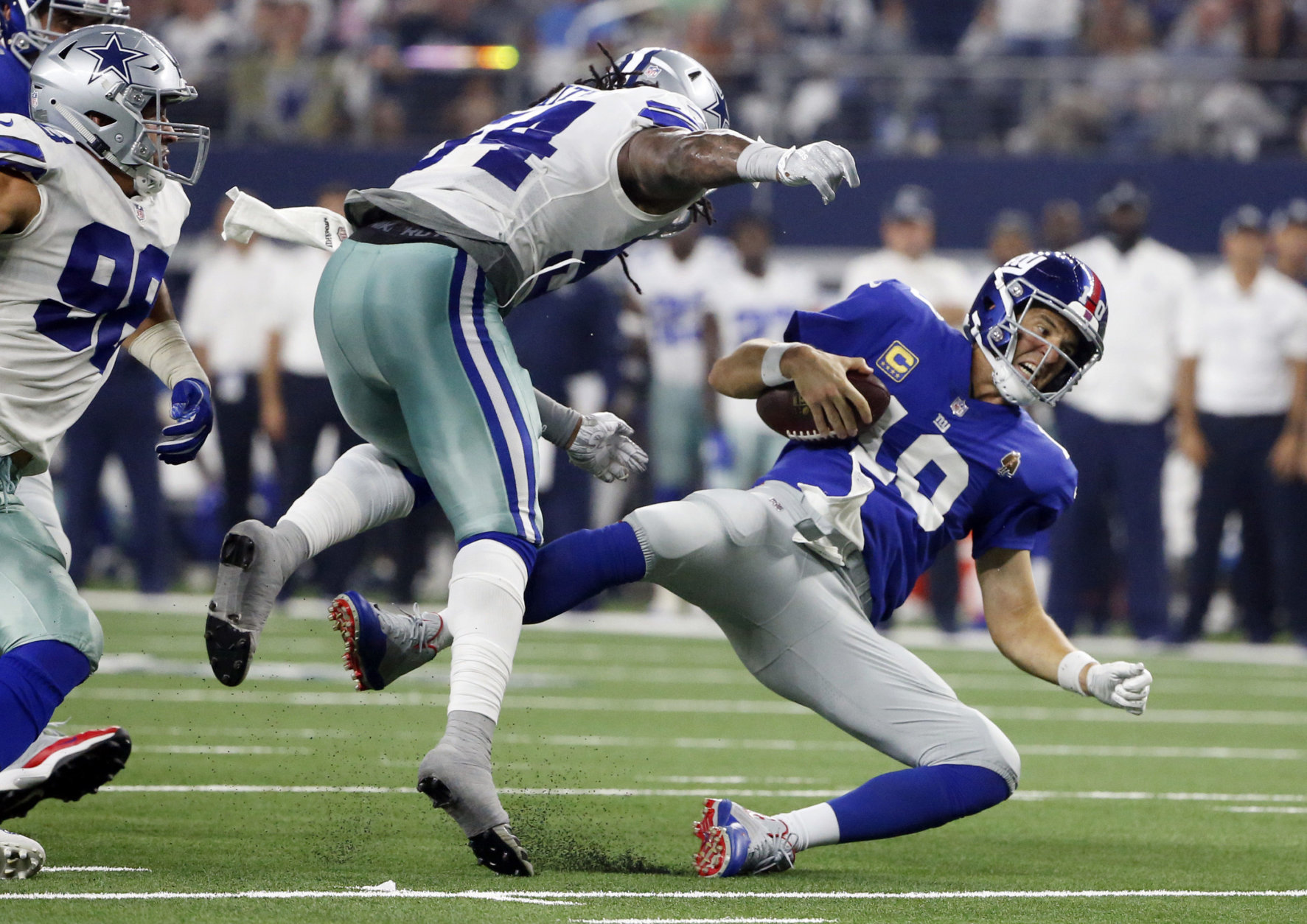 New York Giants quarterback Eli Manning (10) falls after taking a hit from Dallas Cowboys linebacker Jaylon Smith (54) during the second half of an NFL football game in Arlington, Texas, Sunday, Sept. 16, 2018. (AP Photo/Michael Ainsworth)