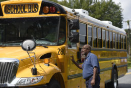 Tim Buffaloe, a chaplain from DayStar Advanced Response Ministerial Operations, talks to a bus driver who said he arrived to transport crime witnesses near the perimeter of a scene where a shooting took place in Aberdeen, Md. on Thursday, Sept. 20, 2018. (AP Photo/Steve Ruark)