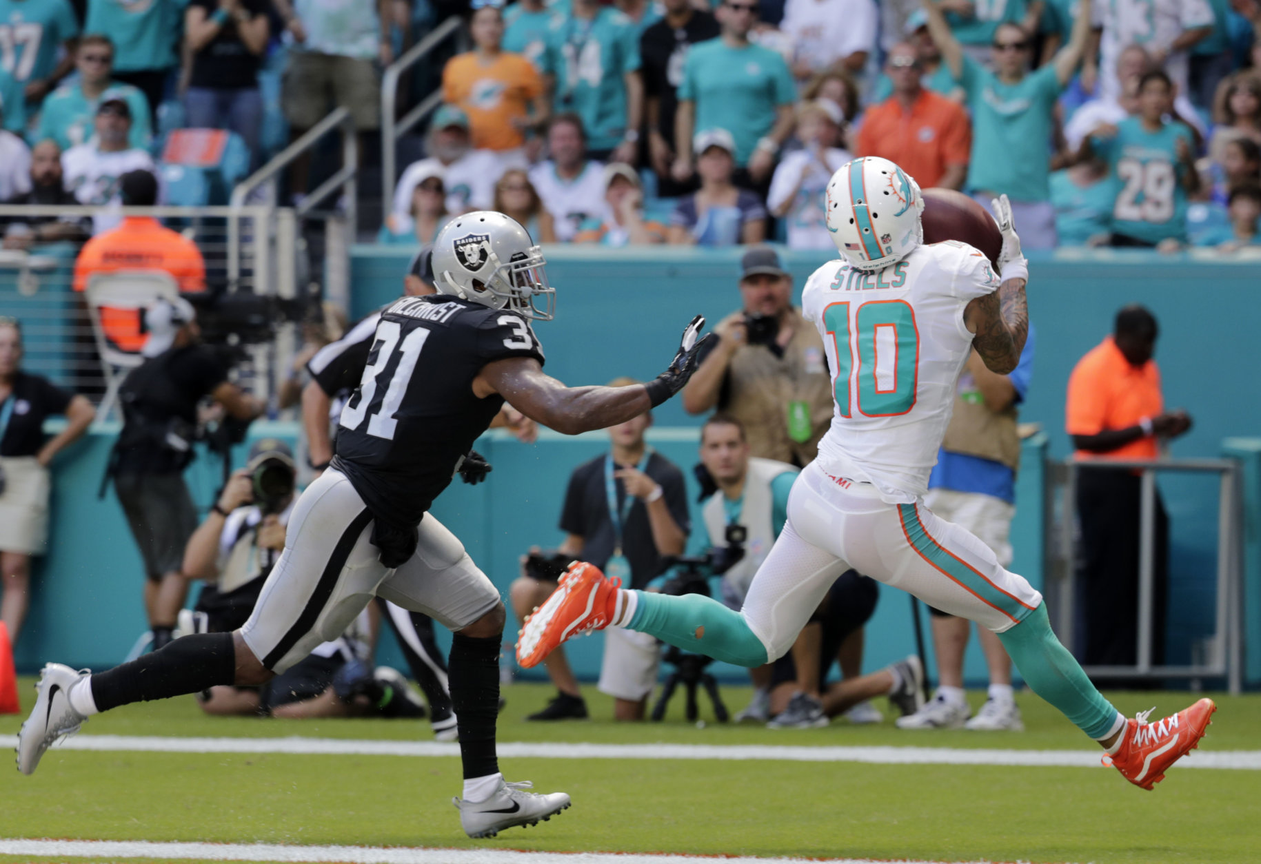 Miami Dolphins wide receiver Kenny Stills (10) catches a touchdown pass as he is pursued by Oakland Raiders defensive back Marcus Gilchrist (31) during the first half of an NFL football game, Sunday, Sept. 23, 2018, in Miami Gardens, Fla. (AP Photo/Brynn Anderson)