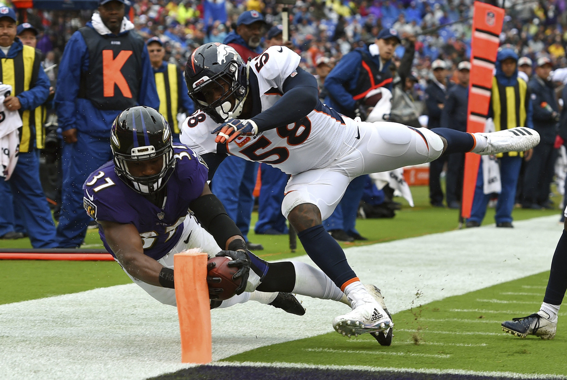 Baltimore Ravens running back Javorius Allen, left, scores a touchdown in front of Denver Broncos linebacker Von Miller in the first half of an NFL football game, Sunday, Sept. 23, 2018, in Baltimore. (AP Photo/Gail Burton)