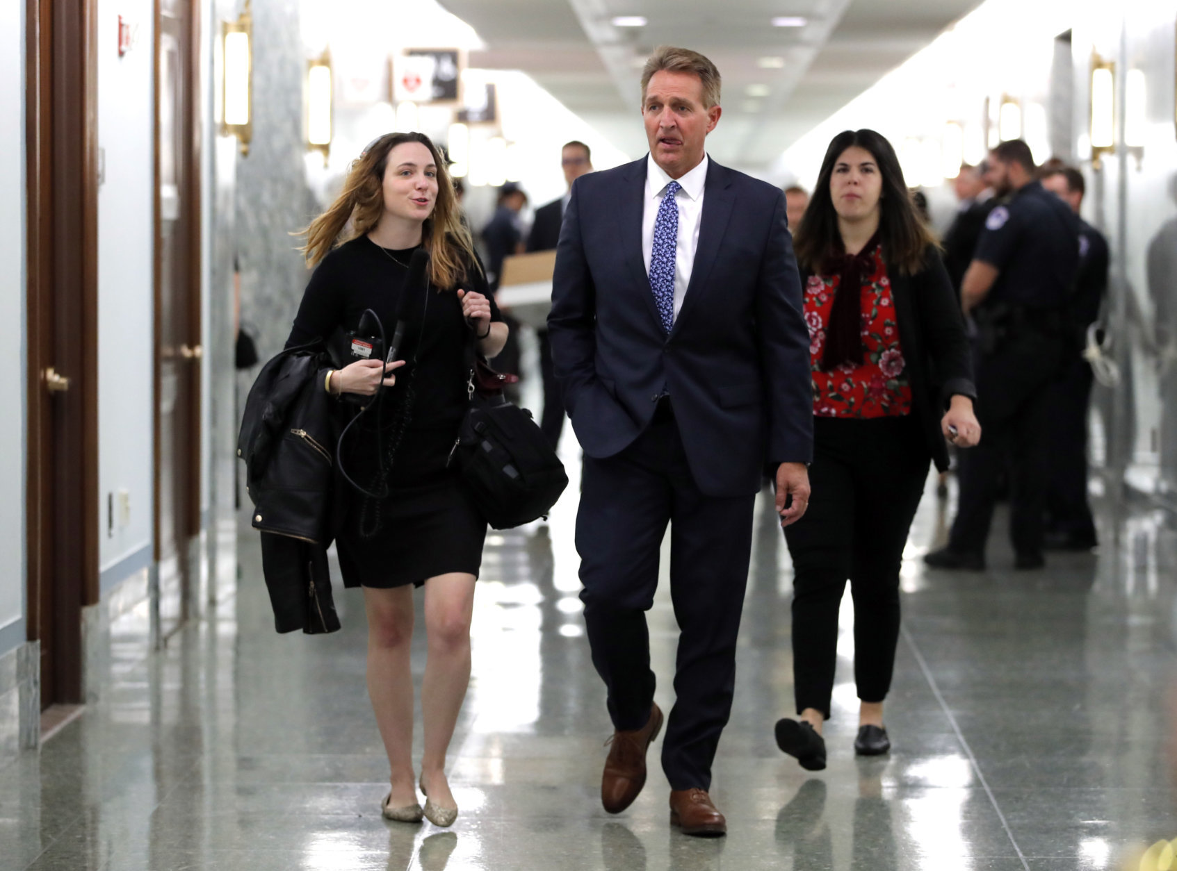 Sen. Jeff Flake, R-Ariz., arrives for the Senate Judiciary hearing on Capitol Hill in Washington, Thursday, Sept. 27, 2018 with Christine Blasey Ford and Supreme Court nominee Brett Kavanaugh.(AP Photo/Carolyn Kaster)