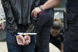 """A supporter of Christine Blasey Ford, with """"Kav-A-Nope"""" written on her hand is arrested for blocking traffic on the street between the Supreme Court and Capitol in Washington, Thursday, Sept. 27, 2018. T (AP Photo/Cliff Owen)"""