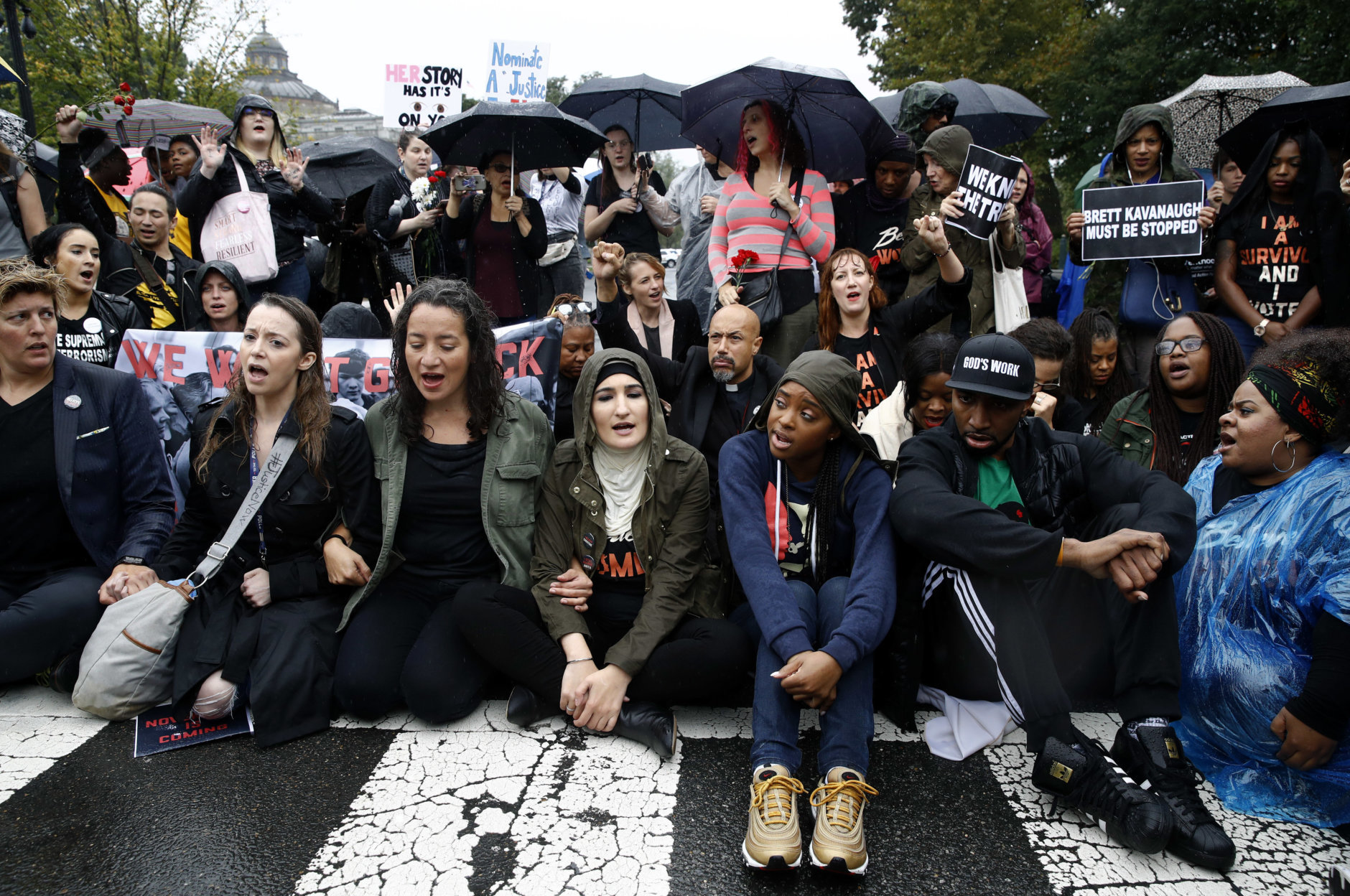 Protesters opposing Supreme Court nominee Brett Kavanaugh sit on a street between the Supreme Court and the U.S. Capitol on Capitol Hill in Washington, Thursday, Sept. 27, 2018. (AP Photo/Patrick Semansky)