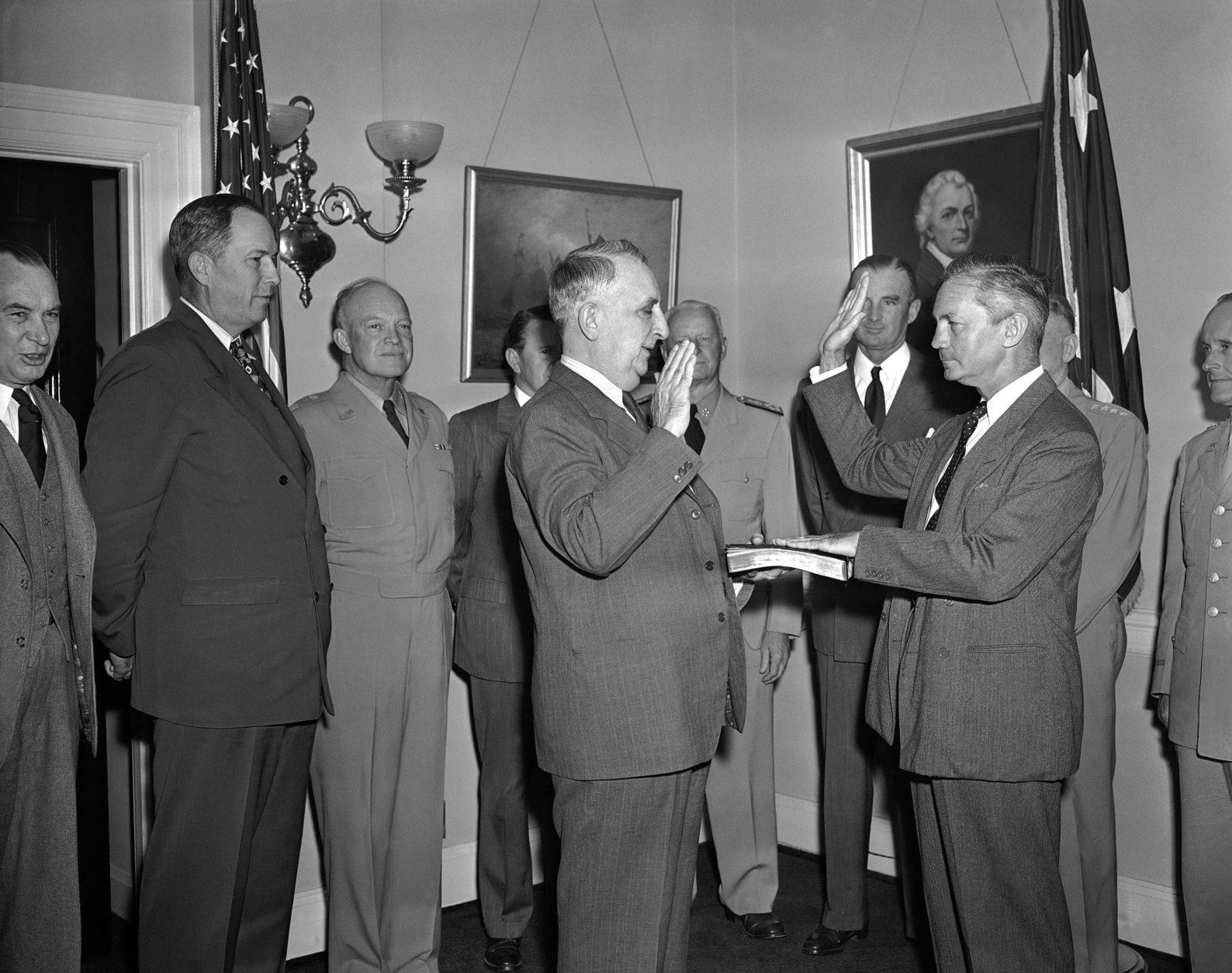 James V. Forrestal (right foreground) takes oath as the nation's first secretary of defense, administered by chief justice Fred M. Vinson (center) at the navy department in Washington on Sept. 17, 1947. Witnessing the ceremony, left to right, are: Secretary of War Kenneth Royall; Army Chief of Staff Dwight D. Eisenhower; Navy Undersecretary John; Chester W. Nimitz; Undersecretary of War S. Stuart Symington and General Carl Spaatz, Air Force Chief. (AP Photo/WX)