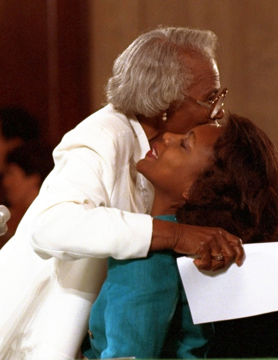 """FILE - This Oct. 11, 1991 file photo shows University of Oklahoma law professor Anita Hill receiving a hug from her mother, Erma, after making opening comments to the Senate Judiciary Committee on Capitol Hill in Washington.  Hill made national headlines in 1991 when she testified that then-Supreme Court nominee Clarence Thomas had sexually harassed her. Now, more than 20 years later, director Freida Mock explores Hill's landmark testimony and the resulting social and political changes in the documentary """"Anita."""" (AP Photo/Greg Gibson, File)"""