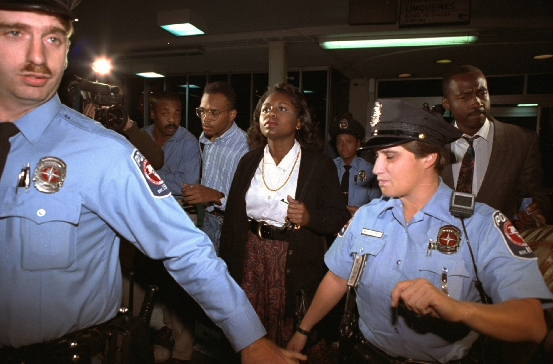 University of Oklahoma law professor Anita Hill, who accused U.S. Supreme Court nominee Judge Clarence Thomas of sexual harassment, leaves Washington's National Airport in Arlington, Va., amid heavy security, Friday, October 10, 1991.  Hill was to testify before the Senate Judiciary Committee Friday.  (AP Photo/Doug Mills)