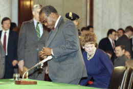 Judge Clarence Thomas prepares for another day of testimony before the Senate Judiciary Committee on Capitol Hill in Washington, Saturday, Oct. 12, 1991. Thomas flatly denied on Saturday that he had ever discussed pornographic movies with Anita Hill or anyone else in the workplace. Thomas? wife, Virginia, sits behind. (AP Photo/Greg Gibson)