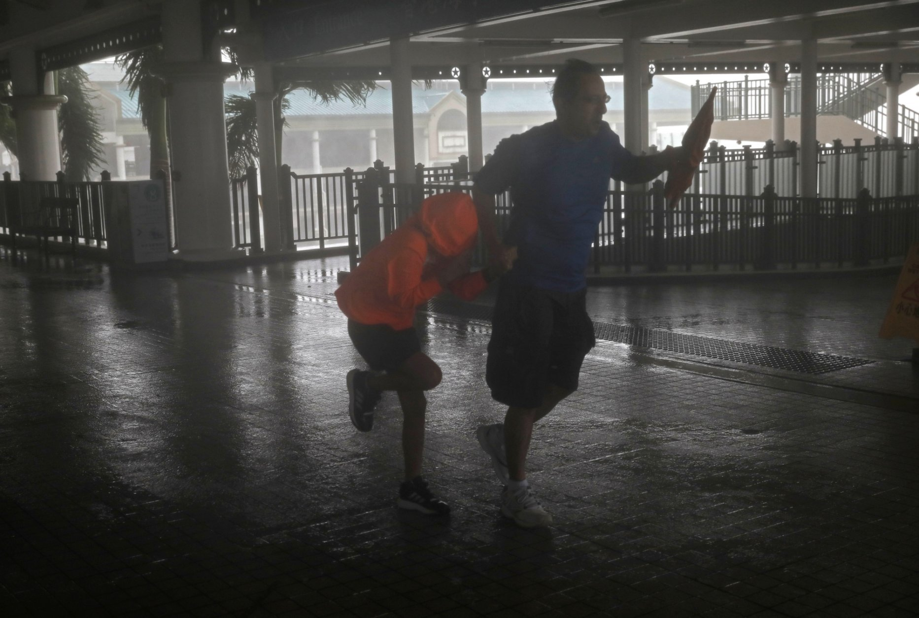 A man and a girl walk against strong winds from Typhoon Mangkhut on a pier on Victoria Habour Hong Kong, Sunday, Sept. 16, 2018. (AP Photo/Vincent Yu)