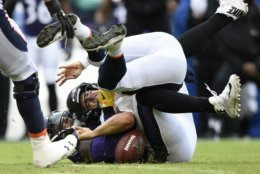 Denver Broncos quarterback Case Keenum, top, fumbles as he is sacked by Baltimore Ravens linebacker Terrell Suggs in the first half of an NFL football game, Sunday, Sept. 23, 2018, in Baltimore. Denver recovered the ball on the play. (AP Photo/Gail Burton)