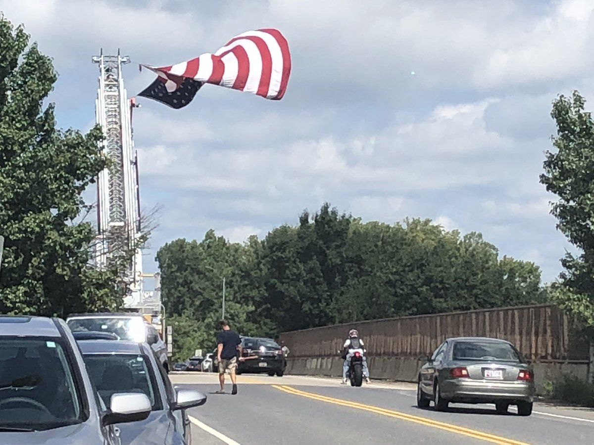 People are waiting to say their final goodbyes to Sen. John McCain. The procession will pass under Church Road in Bowie, Maryland. (WTOP/Melissa Howell)