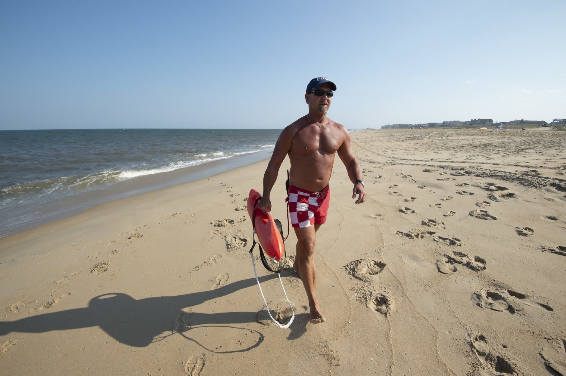 In this Aug. 30, 2018 photo, Fenwick Island Beach Patrol Capt. Tim Ferry walks along the beach in Fenwick Island, Del. The buff high school guidance counselor has been manning the shoreline since 1976, saving lives in between winning medals at international lifeguard competitions and literally writing the handbook on beach safety. (Jason Minto/The News Journal via AP)