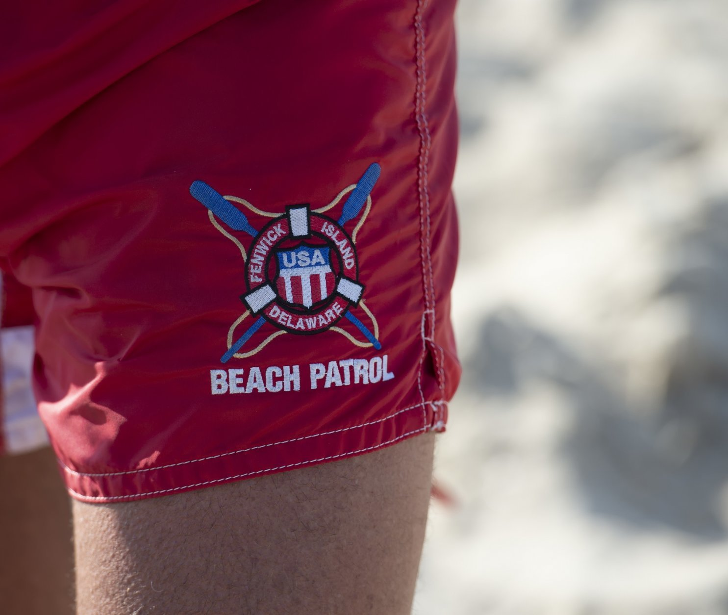 In this Aug. 30, 2018 photo, the beach shorts of Fenwick Island Beach Patrol Capt. Tim Ferry are shown in Fenwick Island, Del. The buff high school guidance counselor has been manning the shoreline since 1976, saving lives in between winning medals at international lifeguard competitions and literally writing the handbook on beach safety. (Jason Minto/The News Journal via AP)